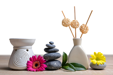 Air freshener with zen pebbles and flowers on white background. Spa and healthcare concept. Stock Photo