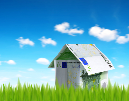 House made from euro money in grass. Stock Photo