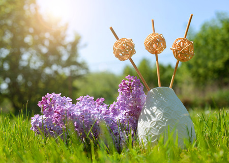 Air refresher bottle with sticks and lilac flowers in grass.