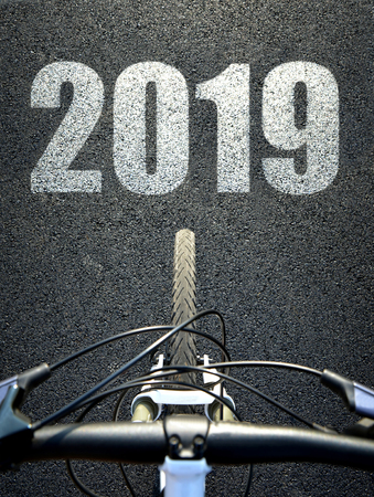 Bicycle on asphalt road. Forward to the New Year 2019. Stock Photo