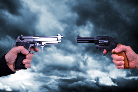 Two hand holding pistol revolvers on the background.