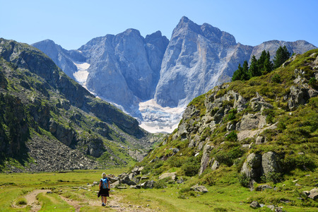 Hiker on a trek in the Pyrenees National Park. Mountain Vignemale in the background. Occitane in the south of France. Stockfoto