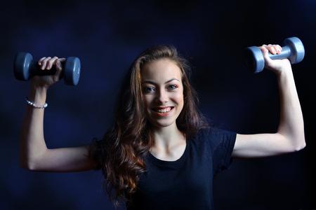 Beautiful caucasian girl holding hands in dumbbells on dark background.