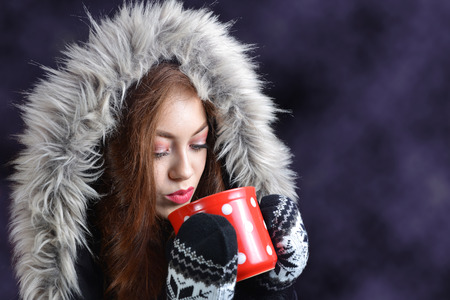 Caucasian girl in winter jacket drinking hot tea from red cup on dark background with copy space.