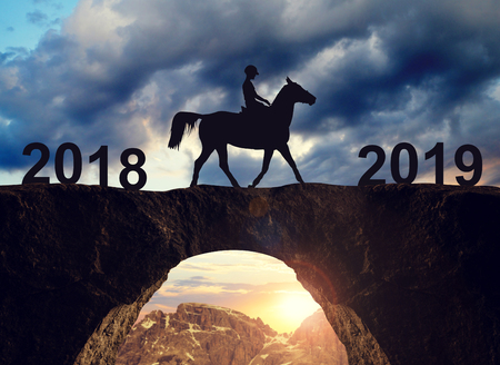 Silhouette of horse rider riding across the bridge to the New Year 2019. Stock Photo