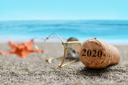 Cork stopper of champagne with number 2020 and starfish on sand beach. Happy New Year concept.