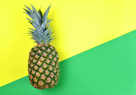 Fresh tropical fruit pineapple on green and yellow paper.