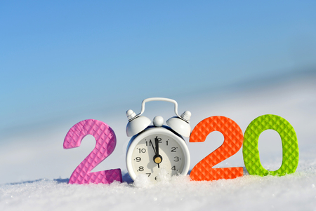 Number 2020 and alarm clock in snow. Happy New Year concept. 免版税图像