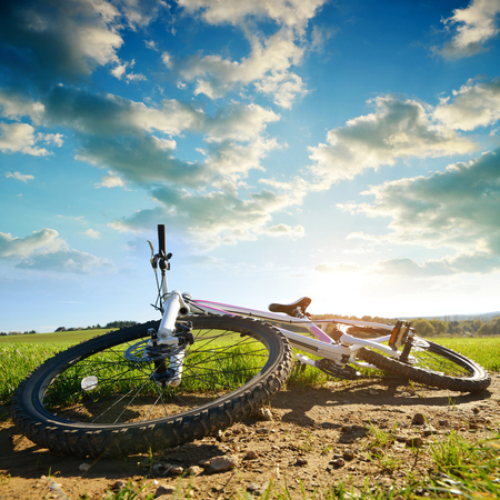Mountain bike MTB lying on rural country trail at sunset.