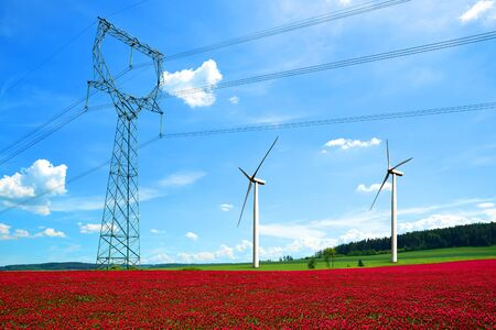 High voltage power lines with wind turbines in Crimson Clovers Field. Renewable Electric Energy Production.