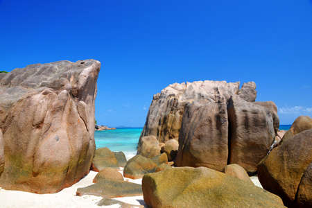 Large granite boulders in Anse Patates beach, La Digue Island, Indian ocean, Seyshelles. Beautiful tropical landscape with sunny sky. Luxury travel destination.