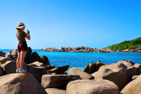 Girl photographing the beautiful coast of the tropical island of La Digue, Indian Ocean, Seychelles.