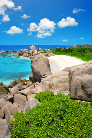 Anse Marron beach with big granite stones in La Digue Island, Seychelles. Tropical landscape with sunny sky.