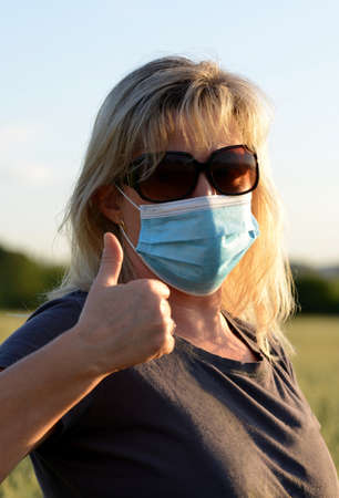 Woman in medical protective mask on her face doing thumbs up gesture. Life during covid-19 pandemic.