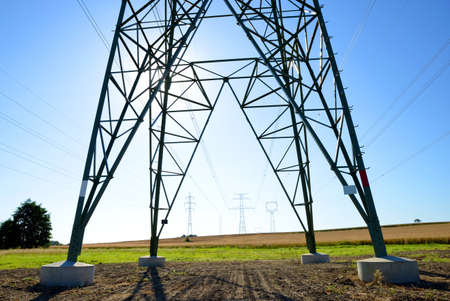 Electric pylon on field. Transmission tower with sunny sky at the background. Zdjęcie Seryjne