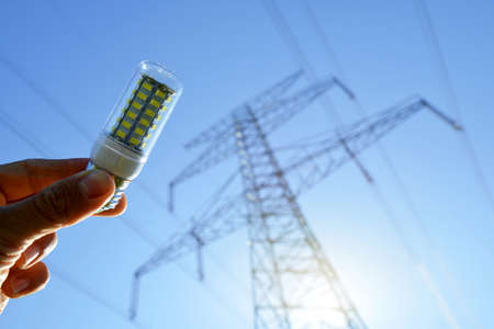 Hand holding eco LED light bulb with transmission tower at the background. Energy saving concept. Zdjęcie Seryjne