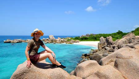 Girl sitting on granite stone near Anse Marron beach, La Digue Island, Indian ocean, Seychelles. Tropical vacation.
