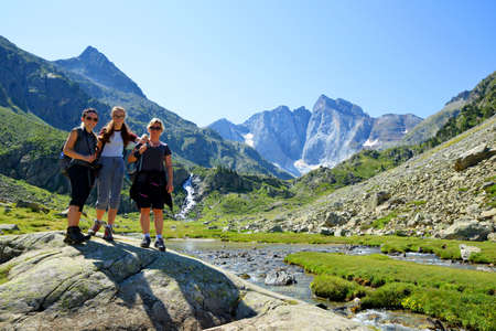 Tourists on a trip in a mountain landscape, Vignemale massif in the background. Pyrenees national park, France.