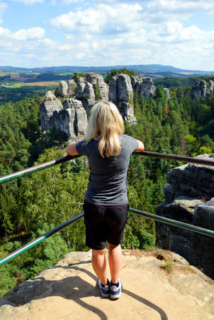 Woman looking at the view of rocky sandstone formations in Hruba Skala, Bohemian Paradise (Cesky Raj), Czechia.