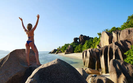 Woman on the beach at sunset in the La Digue Island, Indian Ocean, Seychelles. Vacations concept. Zdjęcie Seryjne