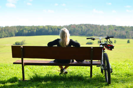 A female cyclist relaxing on a bench after a ride in nature. Zdjęcie Seryjne