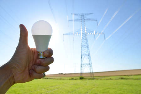 Hand with thumb up holding eco LED light bulb with transmission tower at the background. Energy saving concept.