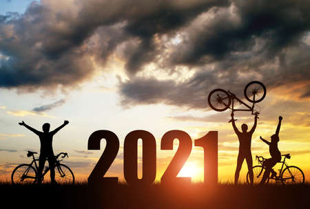 Silhouette of cyclists with bicycles at sunset. Forward to the New Year 2021. Holiday concept.