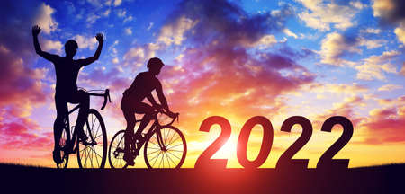 Silhouette of cyclists with bicycles at sunset. Forward to the New Year 2022. Holiday concept. 스톡 콘텐츠