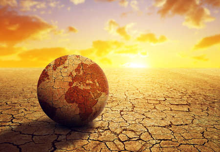 Parched planet earth in the dry landscape with cracked soil at sunset. Global warming or change climate concept. Environmental problems.