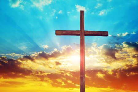 Christian wooden cross at sunset. Religion theme.