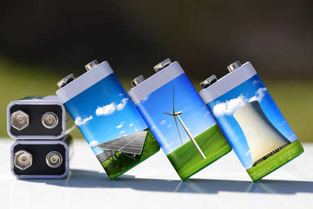 Battery with solar panels, wind turbines and nuclear power plant. Energy resources concept. Stockfoto