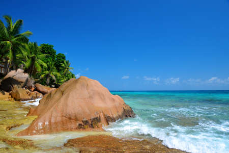 Large granite boulders in Anse Patates beach, La Digue Island, Indian ocean, Seychelles. Beautiful tropical landscape with sunny sky. Exotic travel destinations.
