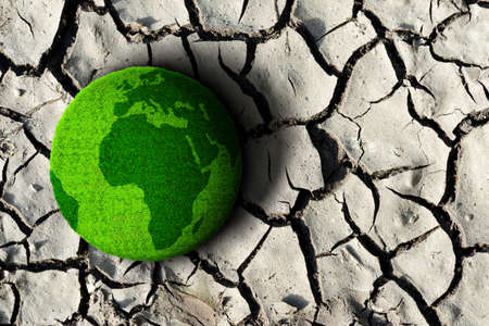 Green planet on the dry cracked soil. Concept of climate change or global warming. Stockfoto