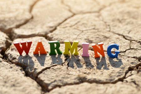 Text Warming on arid cracked soil. Concept of climate change. Stockfoto
