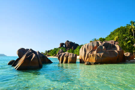 Beatiful beach Anse Source d'Argent with big granite rocks in sunny day. La Digue Island, Seychelles.