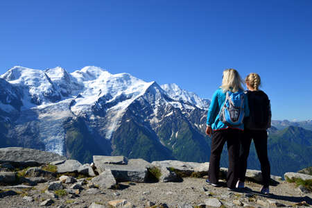 Hikers looking at the Mount Blanc from the summit of Le Brevent. French Alps, Chamonix, France.