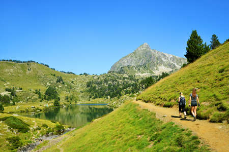 Hikers on a trip in Neouvielle national nature reserve, Lac du Milieu, French Pyrenees. Beautiful summer mountain landscape in the sunny day. Stockfoto