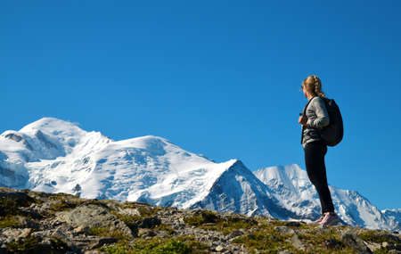 Hiker looking at the Mount Blanc from the summit of Le Brevent. French Alps, Chamonix, France.