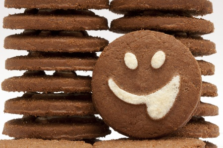 Closeup shot of a brown cookie with smiling face on it