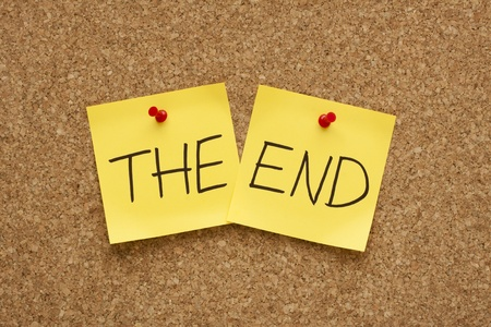 The End written on two yellow sticky notes on an office cork bulletin board