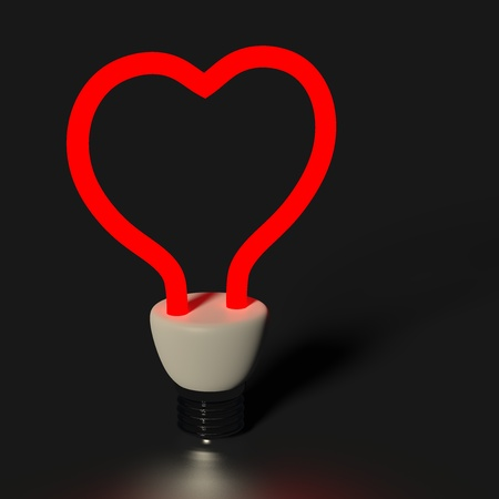 Red heart shaped light bulb isolated on black photo