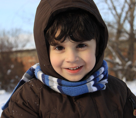Preschool boy with auburn hair and brown eyes is playing with snow outside in a winter day. He is dressed with warm winter clothes, hooded, with gloves and shawl.