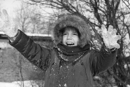 Black and white photo of preschool girl with auburn hair and brown eyes is playing with snow outside in a winter day. He is dressed with warm winter clothes.