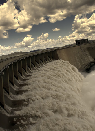 View from one side of the wall of famous Gariep Dam near Norvalspont in South Africa with open spillway and picturesque landscape in the background. Stock Photo