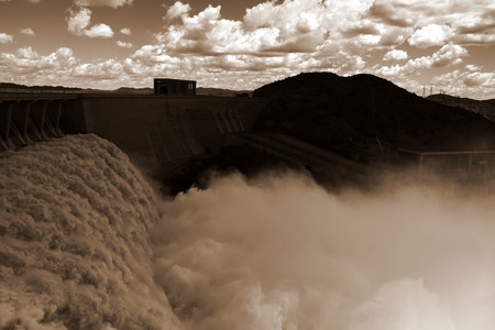 spillway: Black and white view from one side of the wall of famous Gariep Dam near Norvalspont in South Africa with open spillway and picturesque landscape in the background. Stock Photo