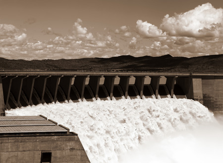 Black and white view from one side of the wall of famous Gariep Dam near Norvalspont in South Africa with open spillway and picturesque landscape in the background. Stock Photo