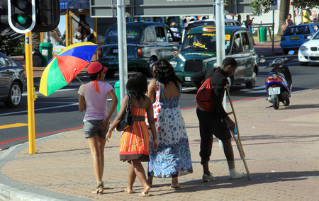 Cape Town, South Africa - December 17, 2010: Group of girls walking past young boy begging on the streets. Editorial