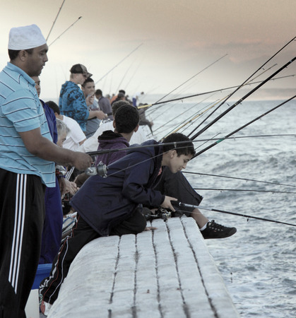 False Bay, Cape Town, South Africa - December 17, 2010: Group of people representing different ethnicities fishing on False Bay waters.