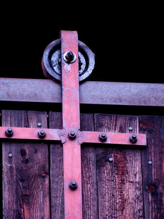 sliding barn door, detail of a wheel on a rail, old brown gate with a metal sliding mechanism, technical solution of the door travel