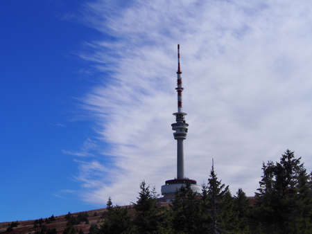 transmitter tower on Praděd with beautiful blue and white sky on an autumn sunny day, Jeseníky Mountains, Czech Republic, travel and mountain hiking, unspoiled nature of rugged mountains